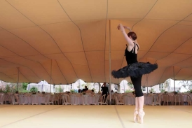 dancer rehearses on stage at Hatch House under chino stretch tent
