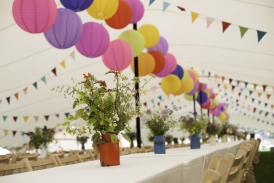 White Stretch tent with long tables and colorful lanterns and bunting
